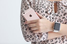 Alushta Russia - October 22 2015: Woman with Apple Watch in the hand holding iPhone 6 S Rose Gold. iPhone 6S and Watch was created and developed by the Apple inc.